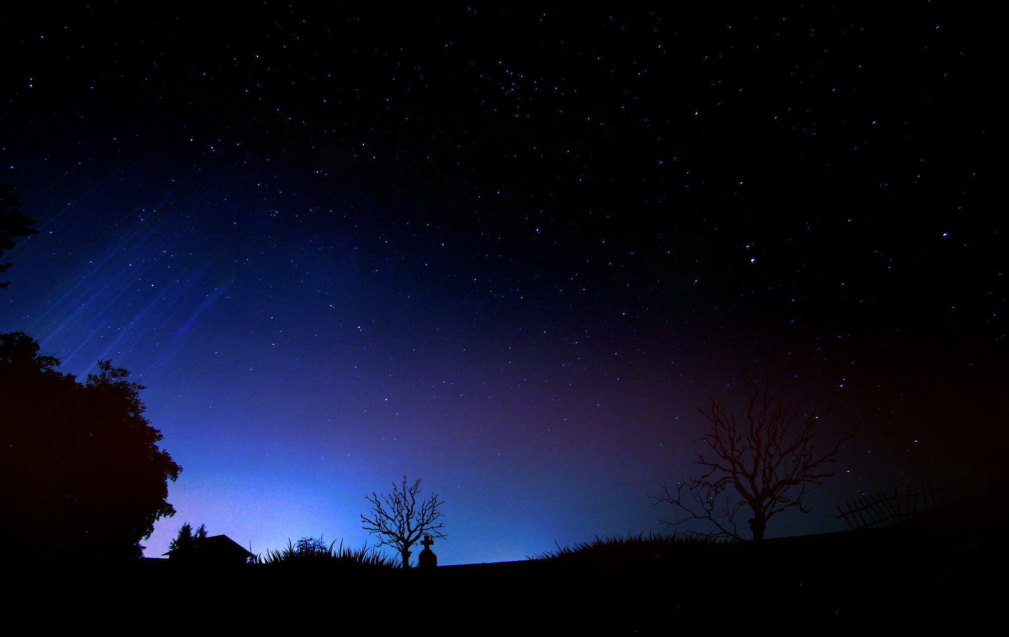 Starry night sky above cemetery free image