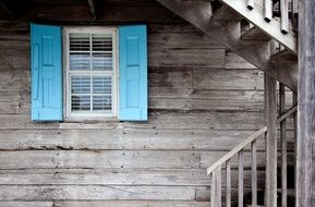 blue shutters at window on grey wooden facade