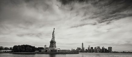 statue of liberty on island in view of new york city, usa