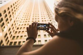 girl taking photography of building with cell phone
