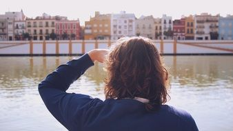 back view of person looking at colorful buildings through river, spain, seville