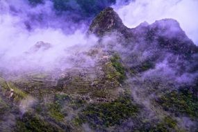 clouds above machu picchu ancient ruins, peru, andes