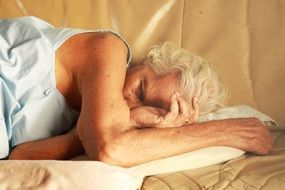 old grey haired woman sleeping on bed