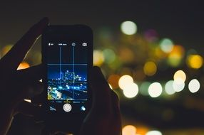 smartphone in person's hands at dusk in city, taking photography