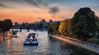 boats on water and people on bank of seine river at sunset, france, paris