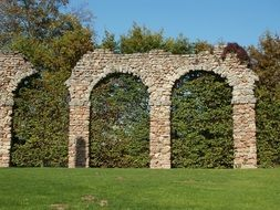 green trees at ancient ruins of roman aqueduct, germany, schwetzingen