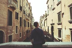 back view of young man on bridge looking at building, italy, venice