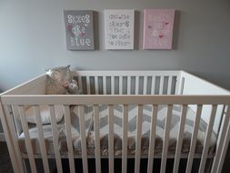 white crib with toys in bedroom