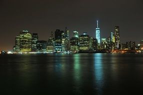 night skyline of new york city with reflection on water, usa, manhattan