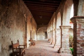 benches in passage of Mission San Juan Capistrano, historic landmark and museum, usa, california