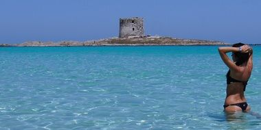 woman in bikini stands in water in view of old tower on island