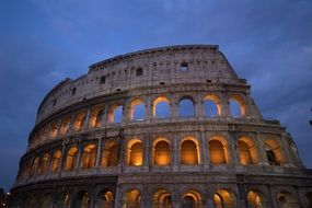 lilluminated colosseum ruin at cloudy evening sky, italy, rome