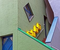yellow mailbox on facade at colorful staircase