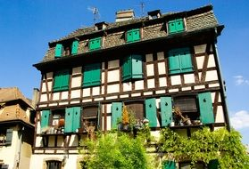 medieval building with green shutters on windows, france, strasbourg