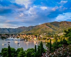 picturesque old town on mountains at lake with ships and boats at port, montenegro