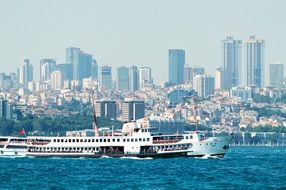 cruise ship with tourists in view of city at waterline, turkey, istanbul