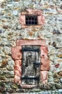 small grated window above closed wooden door in old stone wall, germany
