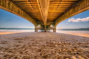 wooden pier above sand beach, bottom view