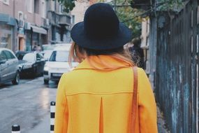 back view of young woman in yellow coat and black hat on street