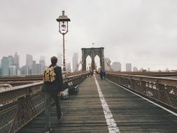 young man walking on brooklyn bridge, usa, manhattan, new york city