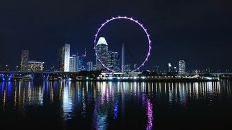 big ferris wheel in night cityscape with lights mirroring on water, singapore