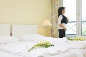 woman stands at window in hotel bedroom, germany, berlin