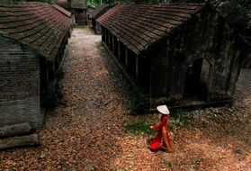 woman in traditional asian clothing walking at old wooden huts