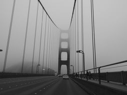 cars and people on bridge in foggy weather