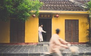 asian man reading paper in doors of yellow building