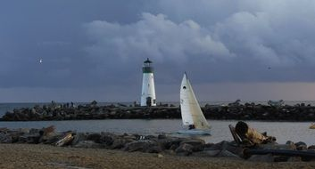 sailing boat on sea in view of lighthouse at cloudy evening