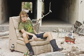 young man in glasses sits on soft chair in dirty yard