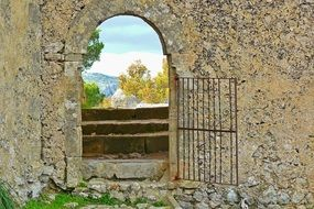 beautiful landscape view through open iron gate in old stone wall, spain, mallorca