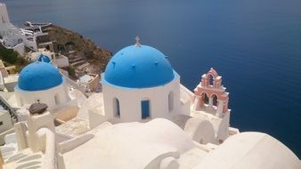 white church buildings with blue roofs at sea, greece