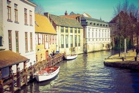 picturesque houses at water and boats on channel, belgium, Bruges