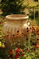 decorative clay pitcher on flower bed in park