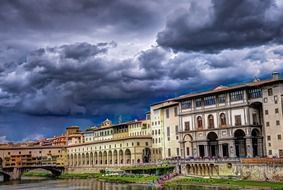 arno river in florence under storm clouds, italy