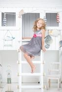 cute child girl sitting on ladder in room