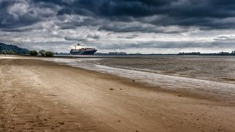 sand beach of elbe river and ships on water at port, germany, hamburg