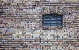 small grated window on old brick wall