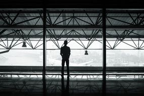 waiting man, silhouette in terminal at window above airplanes