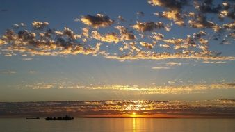 sunset with golden clouds above calm ocean, South Africa, bloubergstrand
