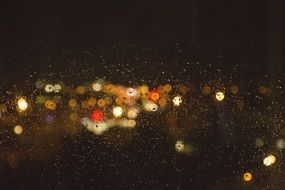 city lights through the window with raindrops