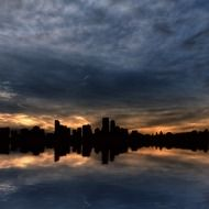 city skyline with reflection on water under cloudy sky