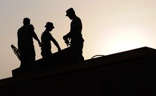 three men silhouettes on roof at sky, construction workers