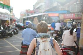 woman with backpack in asian city