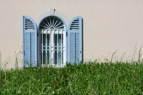 grated arched window with blue shutters on wall at grass