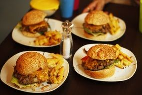 four servings meat burgers french fries