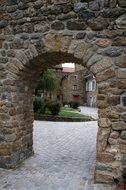 stone arch in wall before old village house, france, bordeaux