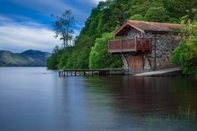 cottage with pier on mountain lake, uk, scotland