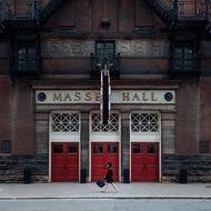 woman walking on pavement at entrance to massey hall, canada, toronto